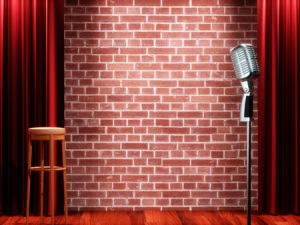 66185360 - vintage metal microphone against red curtain on empty theatre stage. 3d illustration